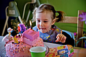 Little girl licking her lips in front of her birthday cake, Otterburn park, Quebec