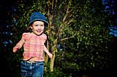 Young girl with blue denim hat running, Otterburn Park, Quebec