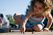 Young girl playing with marbles on sidewalk, Regina, Saskatchewan