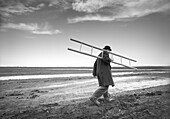 Man Carrying Ladder in Muddy Field, Winnipeg, Manitoba
