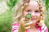 Little girl holding a frog, Simcoe, Ontario