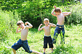 Three brothers making muscle man poses, Simcoe, Ontario