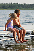 Brother and sister sitting on a lake dock looking into the water, Lac Sante, Alberta