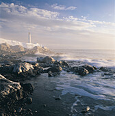 Fog and Rocky Shoreline in Winter with Cap des Rosiers Lighthouse, Northeast GaspÄ Peninsula, near mouth of St. Lawrence River, Quebec