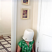 Woman Sitting in Corner with Pot on Head