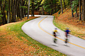 Man and woman cycling on a curvy road through mountain landscape in autumn, Blue Ridge Parkway National Park, Virginia