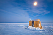Ice Fishing hut under moonlight on frozen Lake Winnipeg, Gimli, Manitoba