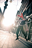 Stylish businessman jumping in the street, Gastown, Vancouver, British Columbia
