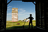 Farmer with a shovel looking out at an abandoned grain elevator, Dankin, Saskatchewan