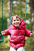 Boy with missing tooth, playing on swing, Gimli, Manitoba