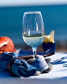 Glass of white wine on an outdoor table, lobster, napkin