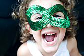 Young girl wear a green glitter mask ans smiling with open mouth