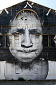 France, Arles, Facade of a warehouse decorated with a giant black and white photography of an old woman