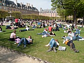 France, Marais District, The Place des Vosges, people resting under the sun, laying on the lawn