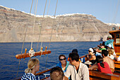 Greece, Aegean Sea, Santorini - Thera, The Albatross Tour Boat full of tourists in front of Santorini and the Thera Cliffs