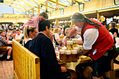 Male waiter with beer steins during  Oktoberfest festival in Munich, Germany