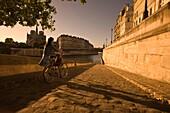 YOUNG WOMAN PUSHING BICYCLE QUAI D'ORLEANS RIVER SEINE ILE SAINT LOUISE PARIS FRANCE