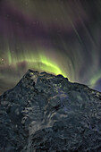 Aurora borealis dances over iceberg from the glacial lagoon jokulsarlon, iceland