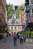 Two women walk up cobblestone streets past shops toward a funicular as car ascends, quebec city quebec canada