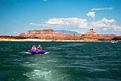 Mother and daughter ride on purple towable tube behind speedboat on lake powell, page arizona usa