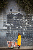 Street Cleaner In Front Of Mural Of Famous Kurdish People, Sulaymaniyah, Iraqi Kurdistan, Iraq