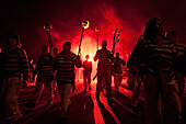 Members Of Borough Bonfire Society Lit From Behind By Flare Marching In Procession At Hastings Bonfire Night, East Sussex, Uk
