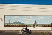 Motorcyclist Riding A Harley Davidson Passing A Cowboy Rancher Mural, Alpine, Texas, Usa