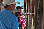 Male Instructor Guides Young Woman About How To Fire Shotgun At Lajitas Resort, Big Bend National Park And Big Bend State Park, South West Texas, Usa