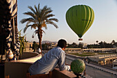 Hotel worker watching hot air balloon from hotel balcony, west bank luxor upper egypt