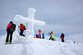 Group of persons back-country skiing standing on the summit of Monte Amaro with snow-covered cross, Monte Amaro, Majella, Abruzzi, Apennines, l' Aquila, Italy