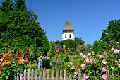 Nun working in an abbey garden, Frauenwoerth church, Frauenchiemsee island, lake Chiemsee, Chiemgau, Upper Bavaria, Bavaria, Germany