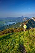 Female hiker ascending to Heimgarten, lake Kochelsee, Benediktenwand, Jochberg and Herzogstand in background, Upper Bavaria, Bavaria, Germany