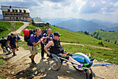 Group of hikers accompanying man in wheelchair, Rotwandhaus alpine hut in the background, mountaineering with handicapped people, Rotwand, Spitzing, Bavarian Alps, Upper Bavaria, Bavaria, Germany