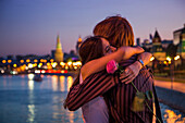 Young couple embracing on a bridge across the Moskva river with illuminated Kremlin buildings in the background, Moscow, Russia, Europe