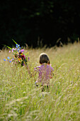 Child, young girl, holding a bunch of flowers in high gras in summer, Germany