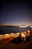 Couple having dinner on a terrace of a restaurant, view over Bay of Budva, Aman Sveti Stefan, Sveti Stefan, Budva, Montenegro