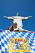 Two young visitors from the German state of Bavaria proudly displaying their heritage flag underneath Cristo Redentor (Christ the Redeemer) statue on Corcovado mountain, Rio de Janeiro, Rio de Janeiro, Brazil