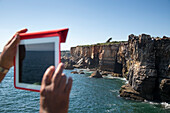 Man taking a photograph of the Boca do Inferno (Hell's Mouth) chasm and cliffs with iPad, Cascais, near Lisbon, Lisboa, Portugal