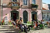 People sitting outside Costa do Castelo restaurant in the Alfama district, Lisbon, Lisboa, Portugal