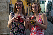 Two hip young women with cocktails in the Bairro Alto district, Lisbon, Lisboa, Portugal