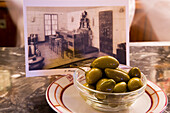Olives and postcard with historic photograph in Harry's Bar, Venice, Veneto, Italy, Europe
