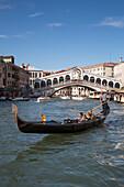Couple enjoying a ride in a gondola near the Rialto bridge on Grand Canal, Venice, Veneto, Italy, Europe