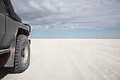 Off-road vehicle passing a salt flat, Kubu Island, Makgadikgadi Pan, Botswana