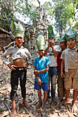 Boys with hats made of banana leaves, temple gate in forest, ruin of Ta Prohm temple, Angkor, Siem Reap, Cambodia