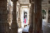 Indian woman wearing sari between the pillars of the jainist main temple Chaumukha Mandir, Ranakpur, Rajasthan, India