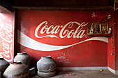Drinking water containers and contrast between coca cola logo and home altar of a restaurant, Khajuraho, Madhya Pradesh, India