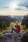 Young woman sitting on a rock while looking at view, Saxon Switzerland National Park, Saxony, Germany