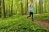 Young woman jogging in a beech forest, National Park Hainich, Thuringia, Germany