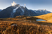 Pasture with mountain lake and the Mont Blanc massif in the evening, Courmayeur, Aosta Valley, Italy