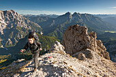 Young man with backpack ascending to Grosser Buchstein, Gesause National Park, Ennstal Alps, Styria, Austria